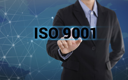 Businessman hand pressing button ISO 9001. sign on virtual screen. business concept. Banco de Imagens