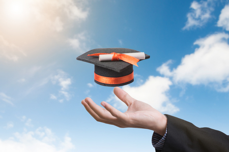 hand holding graduation hat on blue sky background. concept education of new ideas with innovation and creativity.