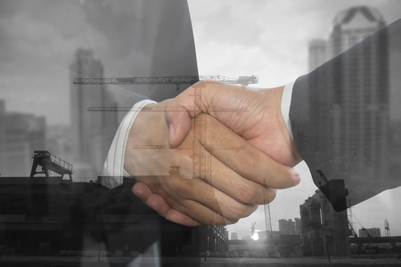 Double exposure of Business people hand shake on building industry construction background. concept business success cooperation.