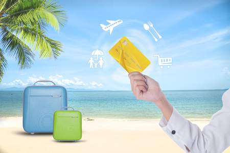 Summer holiday, hand people holding credit card online shopping traveling around the wolrd  and suitcases over exotic tropical beach background. Stock Photo