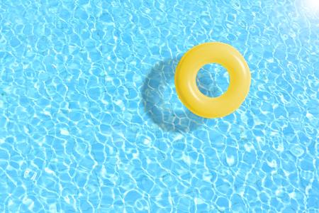 żółty pierścień pływacki pływający w niebieskiej wodzie. koncepcja kolor lato. Zdjęcie Seryjne
