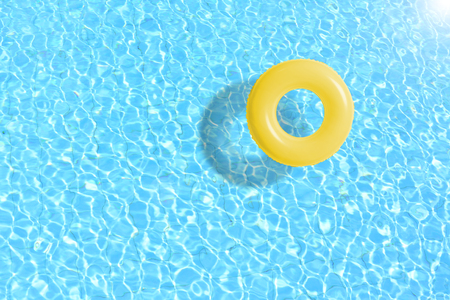 yellow swimming pool ring float in blue water. concept color summer. 스톡 콘텐츠