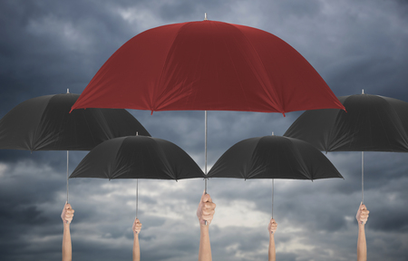 Hand holding red umbrella different among black umbella. insurance policy Life health protection a family conceptaul.