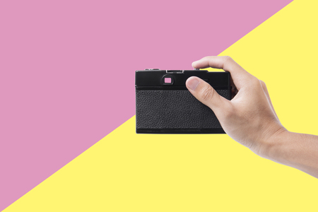 hand holding vintage camera isolated on pink and yellow background. concept photograph for creative and inspiration. Stock Photo