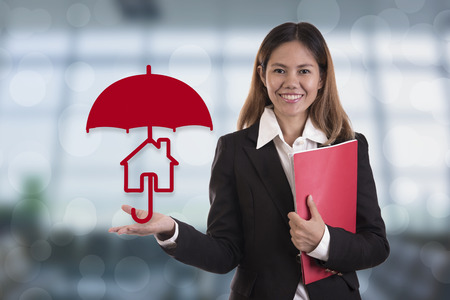 insurer: Sales agent hand holding umbrella protection home. concept accident prevention healthcare insurance.