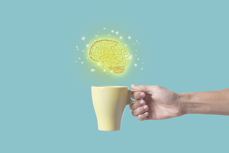 hand holding coffee cup with brain. concept for new ideas with innovation and creativity. Stock Photo