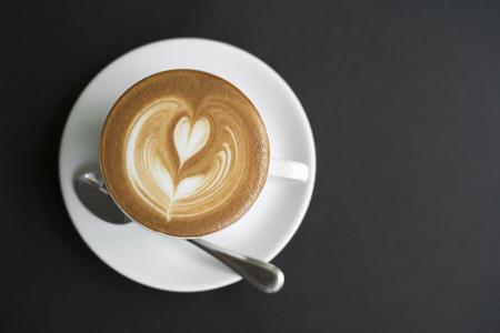 closeup coffee latte art cup on black table