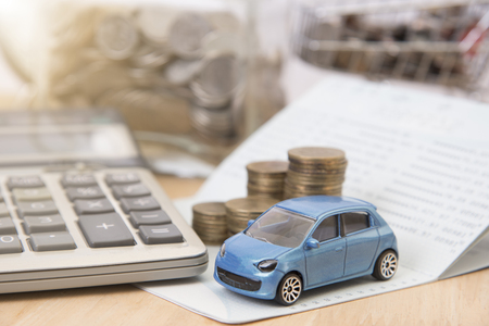 car with calculator and money on wood table. insurance concept.