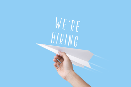 hand holding rocket with we're hiring text. concept employment recruitment hiring.