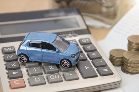 Auto met rekenmachine en geld op houten tafel. verzekering concept. Stockfoto - 91936957