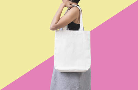 Girl is holding bag canvas fabric for mockup blank template isolated on color background.  Foto de archivo