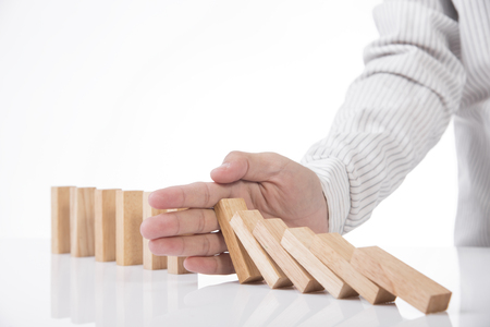 hand stopping wooden block domino. concept prevent and solution. Stock Photo