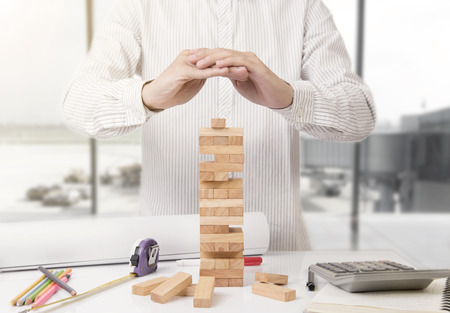 Hand of engineer protection blocks wood tower game. concept safety and  security with insurance. Stock Photo