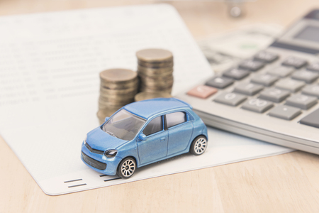 car with calculator and money on wood table. auto loan concept.