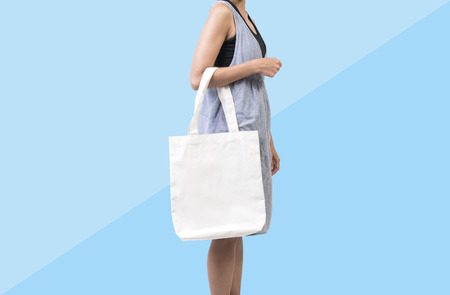 Girl is holding bag canvas fabric for mockup blank template isolated on blue background.