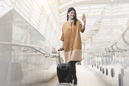 Young woman with travel bag and smart phone walking at the airport for traveler tourism.