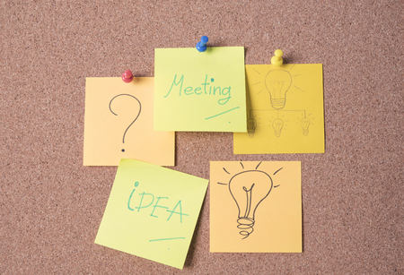 Meeting and idea text on sticky note or post is on cork bulletin billboard.
