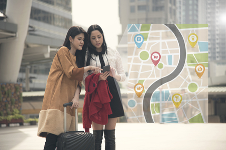 young woman tourist using gps map in a smart phone in the city background.