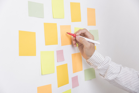 hand writeing sticky note or post is on white bulletin billboard. business, teamwork, brainstorming concept Stock Photo