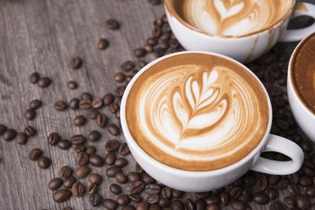 café con leche o capuchino con espuma espumosa, vista superior de la taza de café en la mesa de café. Foto de archivo