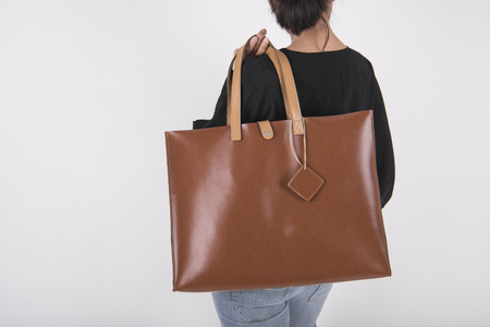 Girl is holding brown leather bag for mockup blank template isolated on gray background.  Stock Photo