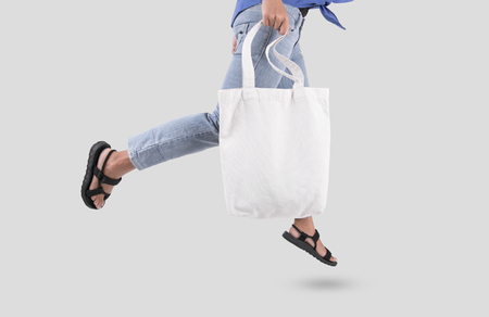 Fille tient le tissu de toile de sac pour le modèle vierge de maquette isolé sur fond gris.