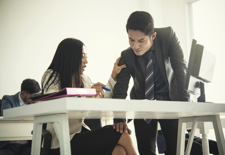 Businessman sexually harassing businesswoman colleague in office. Stock Photo