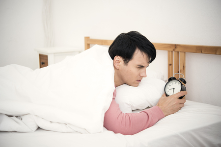 Man wake up doing turn off alarm clock in the morning. He tired and lazy to work.