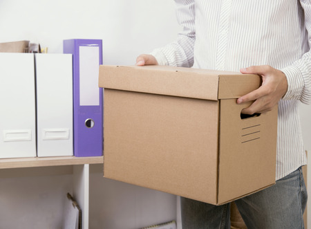 businessman holding personal items box ready moving leaving company. concept layoffs. Stock Photo