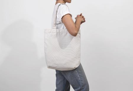 Fille tient le tissu de toile de sac pour modèle vierge de maquette isolé sur fond gris.