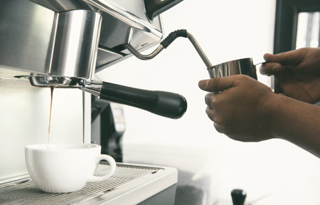Barista using coffeemaker extraction for espresso shot and steam milk in cafe. Stock Photo
