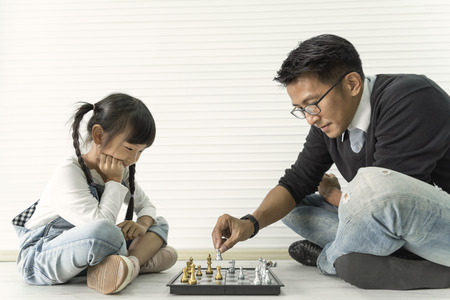 Happy asian family playing chess together. Standard-Bild