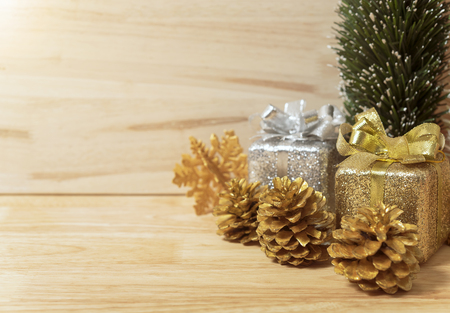 golden pine cones glittered christmas and gift box decoration on wood table background. copy space. Banco de Imagens