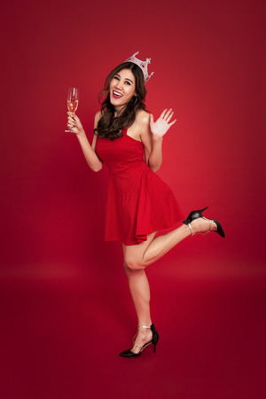 young woman holding glasses of champagne and smiling while celebrating on red background. christmas and happy new year concept. Stock Photo
