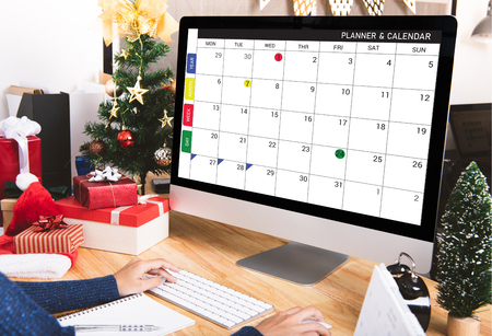 Businesswoman with calendar planner on computer screen in christmas holiday at the office with christmas decoration on table.