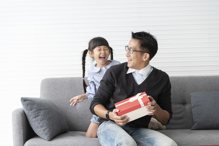 Il padre asiatico fa un regalo per la figlia. confezione regalo a sorpresa di concetto per il compleanno.