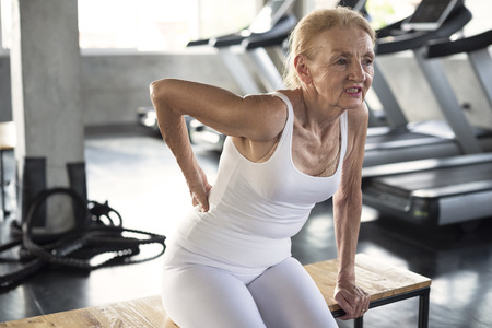 Senior woman injury suffering from backache cause of fitness. Stock fotó - 118194301