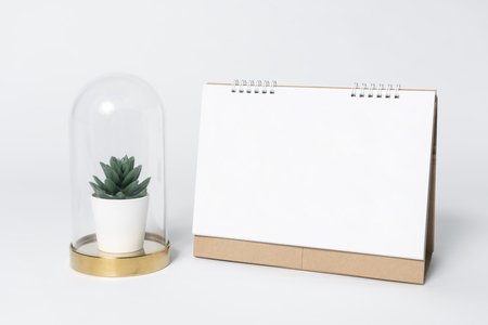 Blank paper spiral calendar and plants in vase for mockup template advertising and branding background. Banco de Imagens