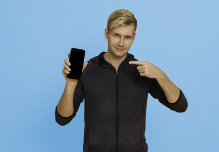 Portrait young man showing mobile phone isolated over blue background.