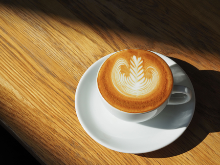 latte or Cappuccino art coffee cup top view on wood table with sunlight in cafe. 免版税图像
