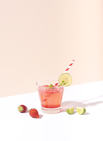 iced strawberry punch cocktail in glass with lime on color background. summer drink.