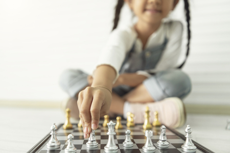 Happy asian girl playing chess at home. 写真素材