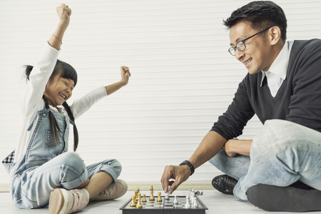 Happy asian family playing chess together at home.