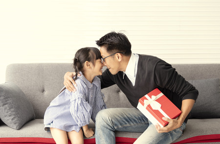 Asian daughter give present for father. concept surprise gift box for birthday.