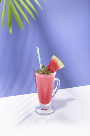Fresh water melon juice and watermelon slice on color background. summer drink. 写真素材