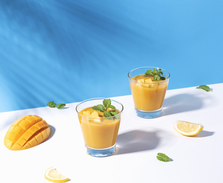 Fresh mango smoothie and ripe mango slice on color background. summer drink. Reklamní fotografie