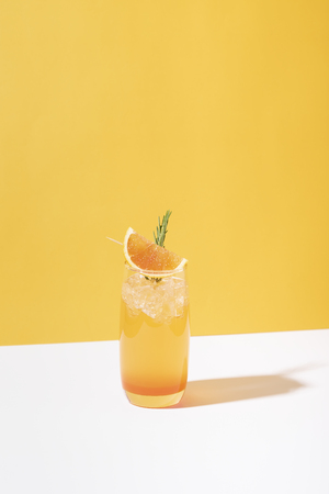 Cold and refreshing orange punch cocktail with orange slice on color background. summer drink. 写真素材