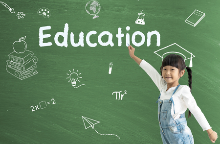 A little asian girl happy smiling on chalkboard background. EDUCATION concept. Imagens