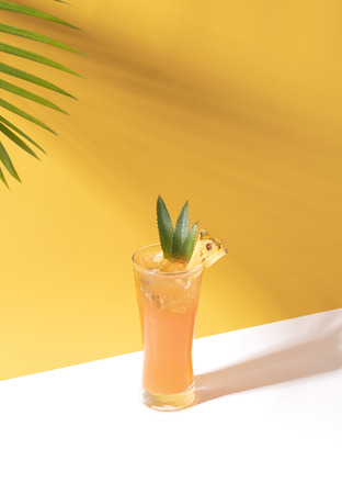 iced pineapple punch cocktail in glass on orange background. summer drink. Imagens