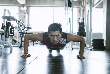 Sport. Giovane uomo atletico asiatico che fa esercizio muscolare push-up in palestra.